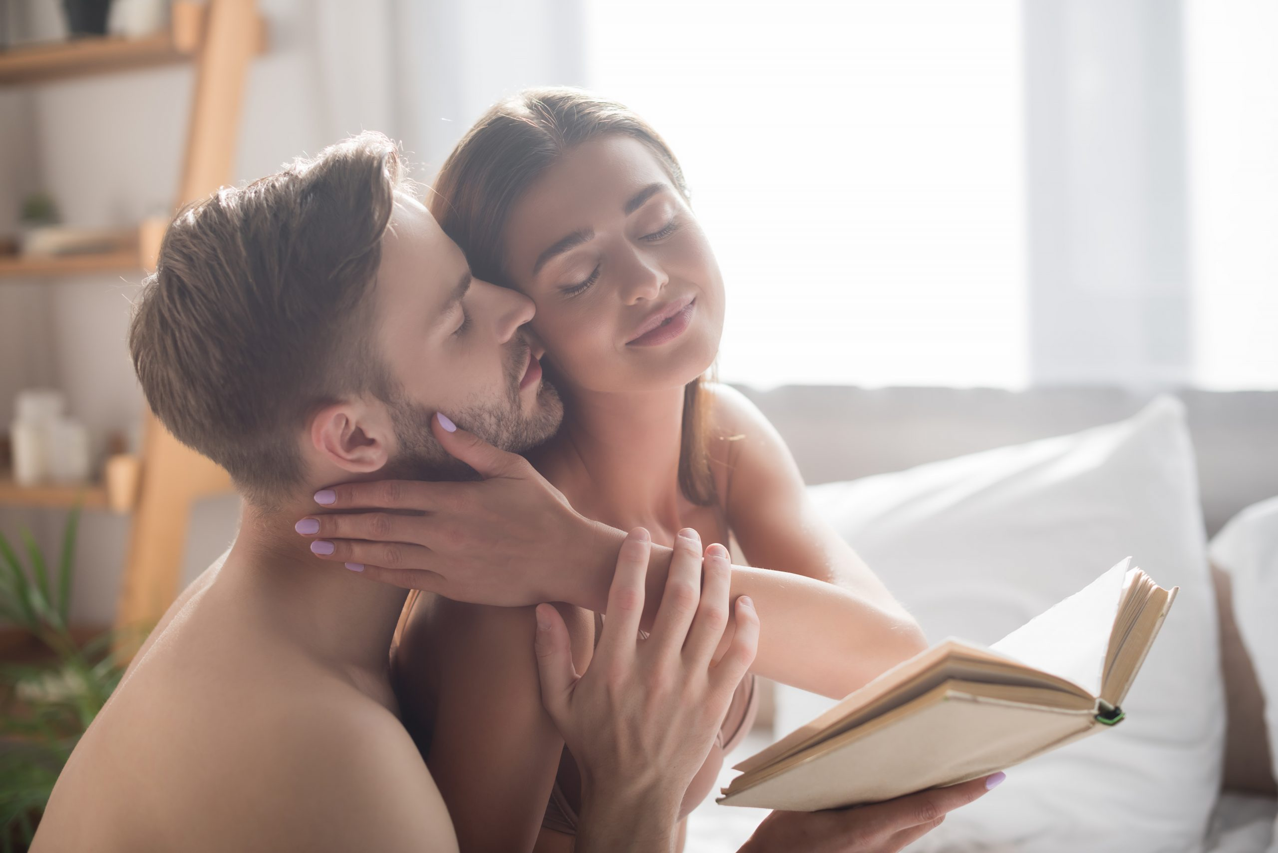 Woman holding book while being softly caressed by her partner